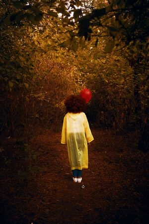 Woman in a yellow raincoat holding a red balloon on the background of forest. Woman walks in the woods in a yellow raincoat, waiting for the rain.