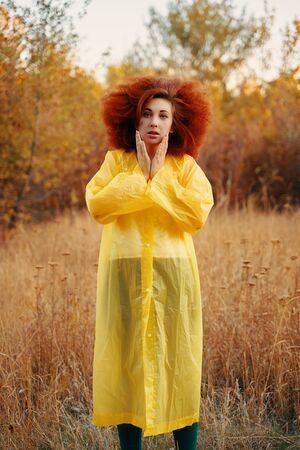 Portrait of a smiling girl dressed in raincoat. Female standing in the field in a yellow waterproof, waiting for the rain.