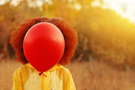 Woman in a yellow raincoat holding a red balloon on the background of forest. Female walks in the forest in a yellow waterproof, waiting for the rain, and holding a red balloon.