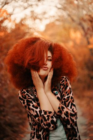 Woman with afro walks in the Park in autumn.