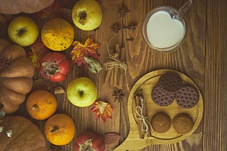 Cookies with milk on the table. Chocolate cookies and cinnamon on the wooden plate with a glass of milk and pumpkin with apple.