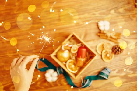 Christmas time. Process of packing gifts for holidays. Woman holds sparkler