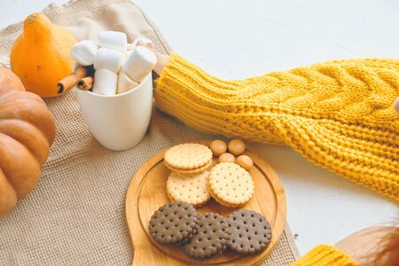 Pumpkin Cookies With Cups Of Coffee. Autumn winter pastries. Cozy atmosphere, warm knitted sweater, girl drink coffee, hands in picture. 版權商用圖片