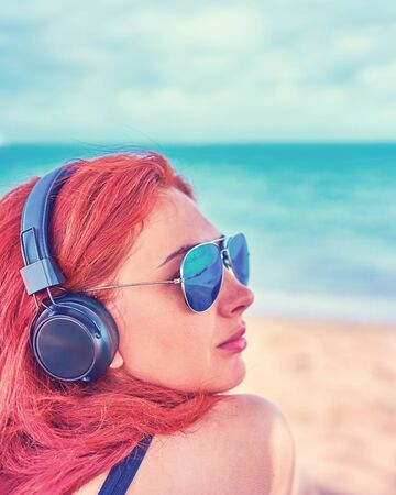 Cool woman listening to music on the beach. The girl enjoys a beautiful view of the sea and listens to music.