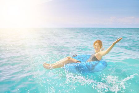 Amazing young woman relax on inflatable ring make water splash in sea water
