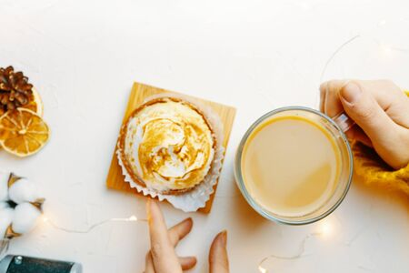 Coffee and cake with cream on the table. Female drinking milk and eating cake.