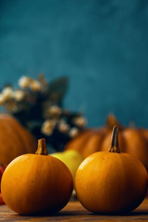 A bunch of pumpkins and apples. Autumn pumpkins with apples on wooden background and leaves. Orange pumpkins on a wooden table in the autumn garden