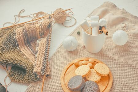 Hot drink with marshmallows and a tube of cinnamon. cookies with Christmas needles. unfinished scarf with knitting needles Фото со стока