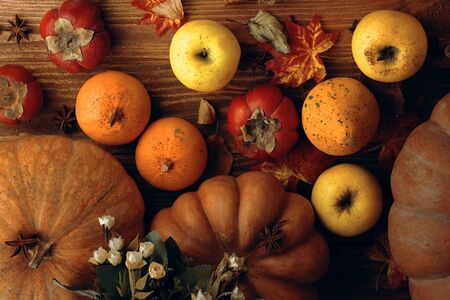 Pumpkins and apples. A bunch of pumpkins and a few apples lie on a wooden table top view. 版權商用圖片