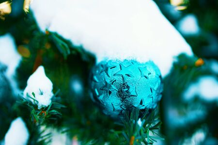 Decorated Christmas tree. Close-up of a blue bubble hanging from a decorated Christmas tree.