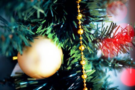 Yellow ball Christmas tree toy close up. Christmas ornament with lighted tree in background. 版權商用圖片