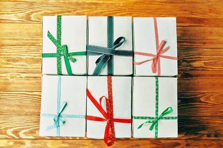 Stack of gift wrapped Christmas presents. A stack of gifts of white colors tied with different ribbons on a wooden background. 版權商用圖片