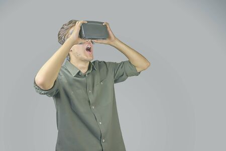 Young man in shirt enjoys and amazed by virtual reality glasses in front of light grey background