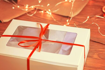 Christmas composition with present box. A Christmas gift box with a red ribbon stands on a wooden table. 版權商用圖片