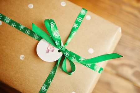 Little tag with Christmas wishes and gifts. Label on the gift box that says Merry Christmas. 版權商用圖片