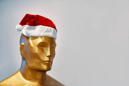 The man in the Christmas hat. A Golden statue of Oscar stands in a Christmas hat.
