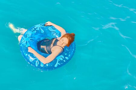 Beautiful young woman relax on blue inflatable ring in sea water 版權商用圖片
