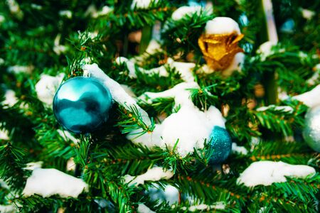 Decorated Christmas tree. Close-up of blue and gold balls with snow hanging from a decorated Christmas tree. 版權商用圖片