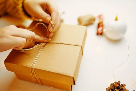 Woman packaging Christmas gift box. Female ties a knot on a box with gifts for Christmas.