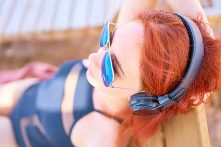 Cute woman listening to music on the beach. Red-haired young woman lying on the beach, relaxing on a lounger and listening to relaxing music. 版權商用圖片