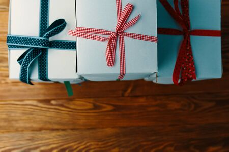 Stack of gift wrapped Christmas presents. A stack of boxes of white colors tied with different ribbons on a wooden background. Flat lay.
