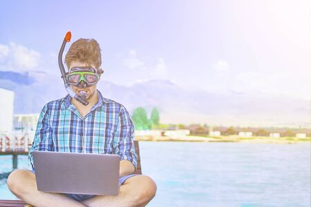 A man in an underwater mask, on vacation at sea, working at a computer. 版權商用圖片