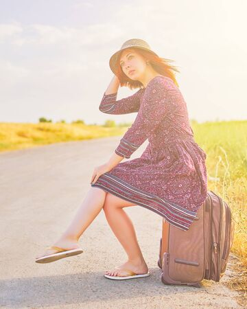 Amazing woman in summer dress and hat hitchhiking with suitcase on the road. Cute female sitting on Luggage waiting for car. Trip concept 版權商用圖片