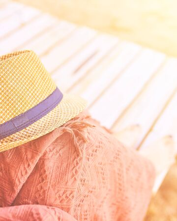 Straw hat on a hot day off on womans leg with plaid