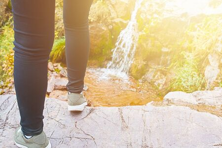 Female hiker walking in mountains forest. Beautiful brook, waterfall in the mountains in the forest.