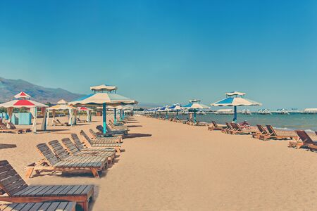 Sunbeds on the beach. A row of sun umbrellas with seats on the lake shore.