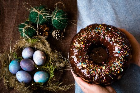 Woman holding chocolate cake with powder next to space galactic Easter eggs in nest next to bump and green filler Stock Photo - 138015844