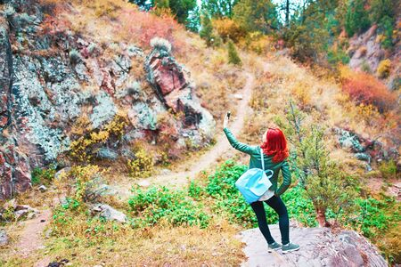 Female hiker taking selfie in mountains forest. A woman saw a beautiful landscape and decided to take a photo.