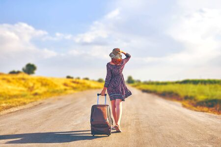 Amazing woman in summer dress and hat hitchhiking with suitcase. Female walking on the road with Luggage. Freedom concept
