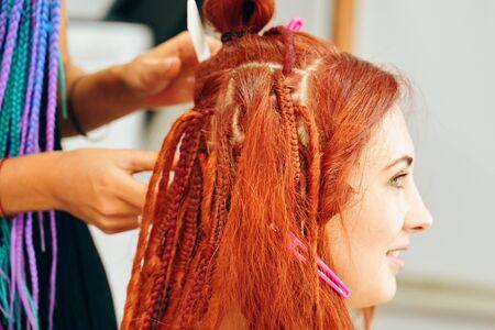 Barber braids safe dreadlocks. Beautiful girl making trendy braids dreadlocks. kanekalon