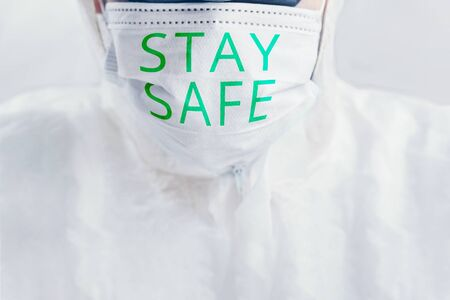 Virologist. Human bio suit and protective mask with the inscription Stay safe. Stockfoto