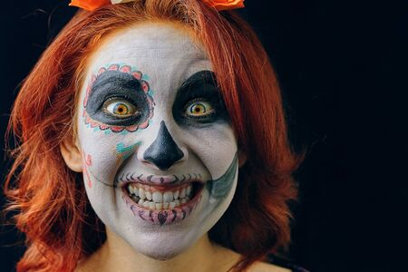 Young woman in day of the dead mask skull face art make-up and red hair showing teeth on dark background close up. Halloween concept, mad smile