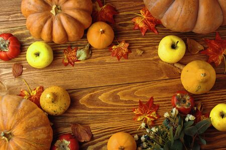 A bunch of pumpkins and apples on wooden desk. Flat lay with copy space Standard-Bild