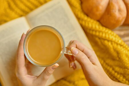 Top view of coffee with milk in woman hands on a table, pumpkin, book on wooden textured desk. Seasonal background, autumn theme