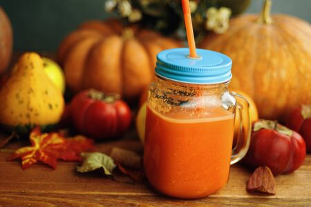 Cup of pumpkin juice with tube on wooden table with apples and big pumpkins Banque d'images