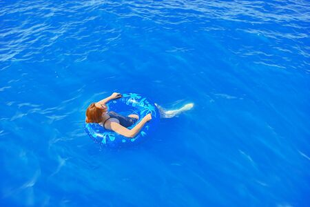 Amazing young woman with inflatable ring relaxing in blue raging ocean Foto de archivo