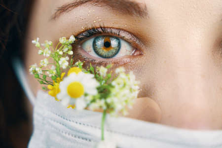 Macro eye portrait. Young attractive woman in floral face mask of flowers looking at camera in a studio in a mask during the coronavirus pandemic, new trend spring fashion.