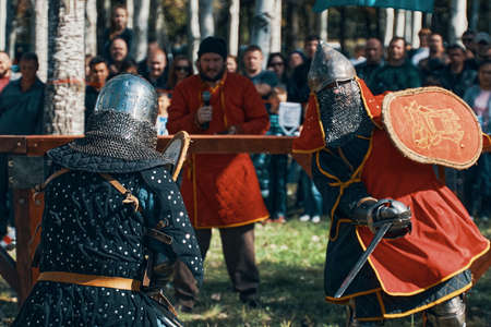 Reconstruction of medieval tournaments of knights. Knights in armor and helmets, fighting with swords and shields in the arena. Festival of historical clubs. Bishkek, Kyrgyzstan - October 13, 2019 新闻类图片