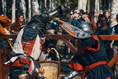 Two knights fight with swords. Reconstruction of a medieval battle in the arena with the audience. Festival of historical clubs. Bishkek, Kyrgyzstan - October 13, 2019