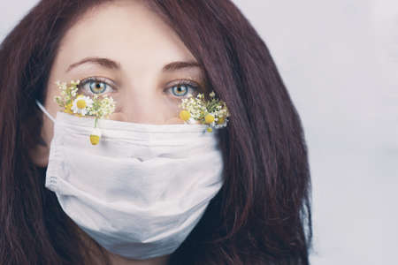Young attractive woman in floral face mask of flowers looking at camera in a studio in a mask during the coronavirus pandemic, new trend spring fashion. 免版税图像