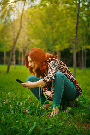 Red-haired young adult woman enjoys mobile photography in the Park taking pictures of flowers