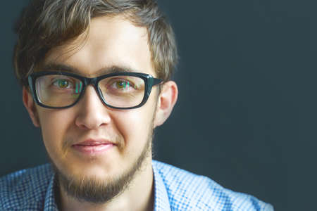 Man software developer engineering student in glasses. Close up smiling young businessman wearing eyeglasses, looking at the camera against gray wall background with copy space.