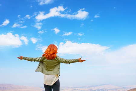 Happy beauty red-haired woman in green jacket open hands outdoors enjoying freedom nature on sky with clouds background. 免版税图像