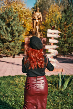 Stylish young woman stands with her back against the background of a monument in the park. A young woman with red hair wearing a beret and a leather pencil skirt.