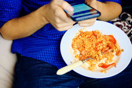 Man uses a smartphone in social networks while dining in a blue shirt and jeans sitting on a binbag during breakfast.