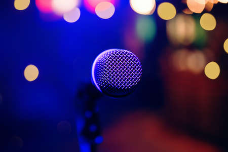 Microphone in the restaurant or night club for stand up show with blur colorful background for any purpose.